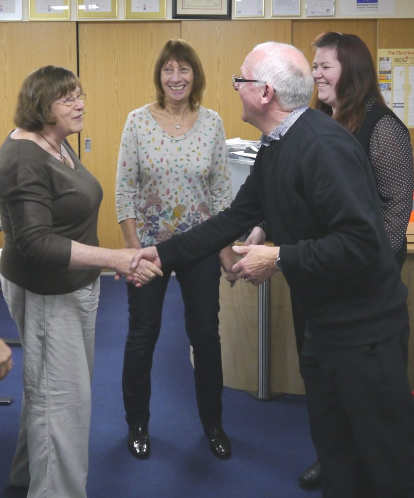 Two people shaking hands while others watch