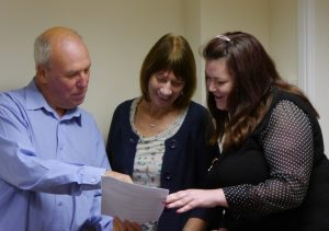 Picture of three people looking at a piece of paper