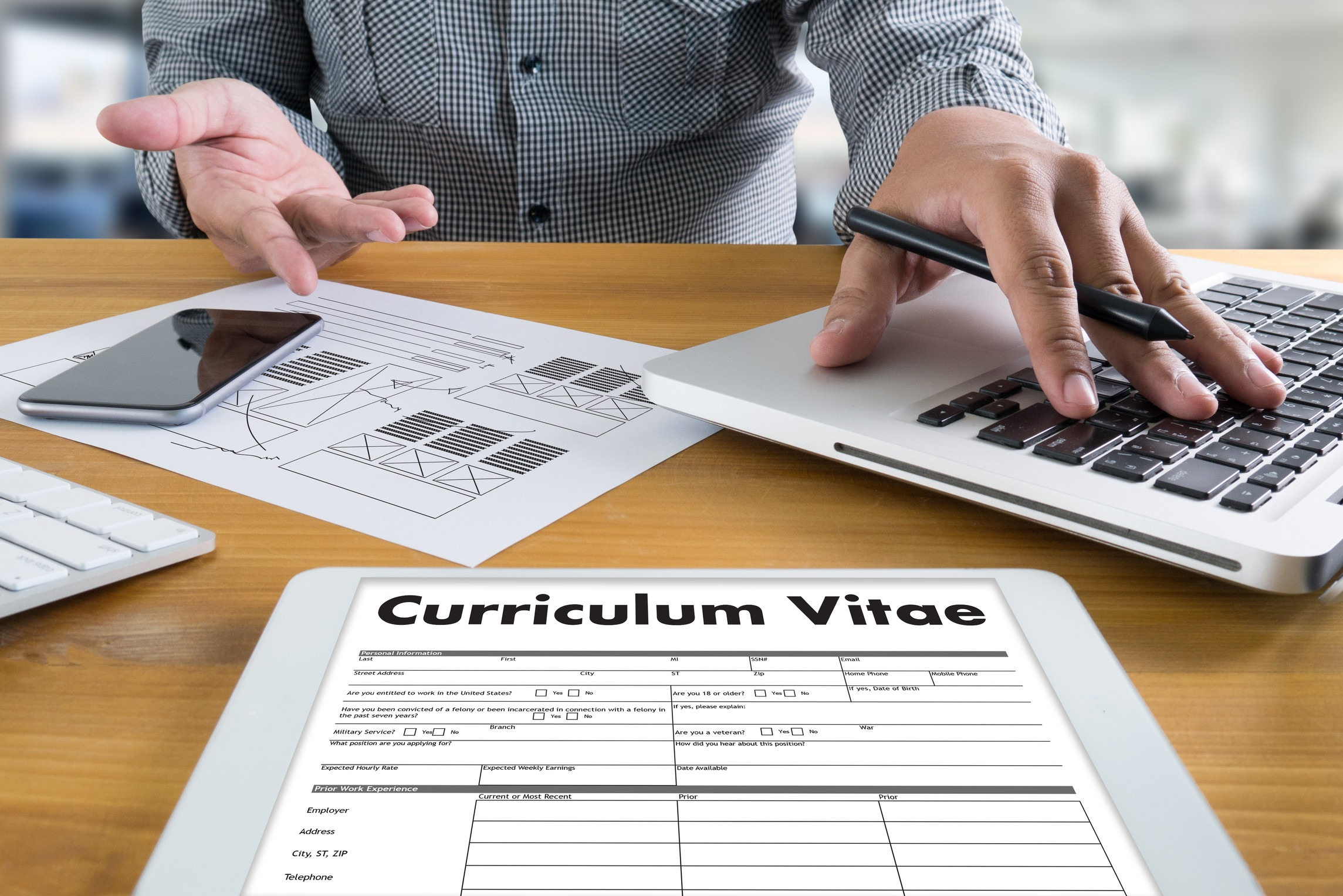 Picture of a man with a CV and a pen and papers